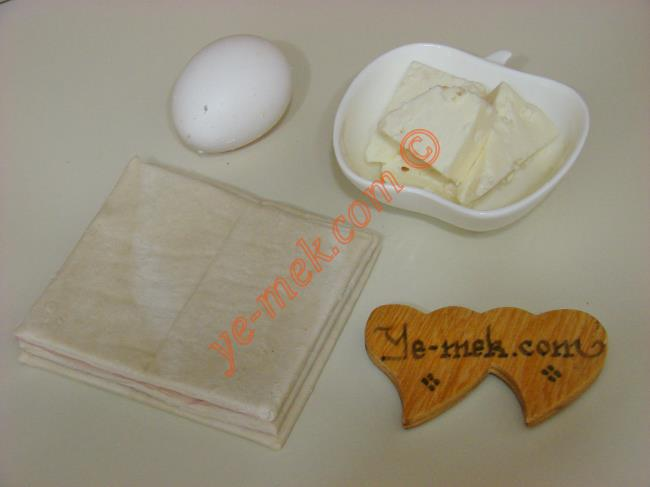Milföyden Fiyonk Börek İçin Gerekli Malzemeler :  <ul> <li>3 adet kare milföy</li> <li>1 dilim beyaz peynir</li> <li><strong>Üzeri İçin:</strong></li> <li>Yumurta sarısı</li> </ul>