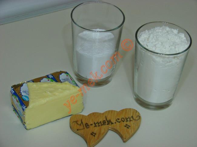 Üç Malzemeli Un Kurabiyesi İçin Gerekli Malzemeler :  <ul> <li>125 gr tereyağı (oda sıcaklığında)</li> <li>1/2 su bardağı pudra şekeri</li> <li>1,5 su bardağı un</li> <li><strong>Üzeri İçin:</strong> <li>Pudra şekeri</li> </ul>