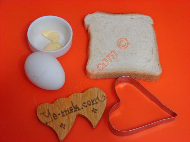 Ekmek İçinde Yumurta İçin Gerekli Malzemeler :  <ul>  <li>1 adet yumurta</li> <li>1 dilim tost ekmeği</li> <li>1 tatlı kaşığı tereyağ</li> <li>Tuz</li> <li>Pulbiber</li> </ul>