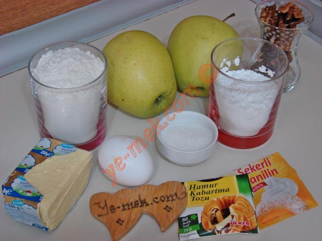 Elmalı Rulo Kurabiye İçin Gerekli Malzemeler :  <ul> <li>125 gr tereyağı (Oda sıcaklığında)</li>         <li>2,5 yemek kaşığı toz şeker</li>         <li>Yarım su bardağı nişasta</li>         <li>1 adet yumurta</li>         <li>Yarım paket kabartma tozu</li>         <li>1 paket vanilya</li>         <li>1 su bardağı + 2 yemek kaşığı un</li> <li><strong>İç Harcı İçin:</strong> <li>2 adet büyük boy elma</li>         <li>2 yemek kaşığı toz şeker</li>          <li>1 çay kaşığı tarçın (arttırabilirsiniz)</li>          <li>Küçük çay bardağı az dövülmüş ceviz</li>  </ul>