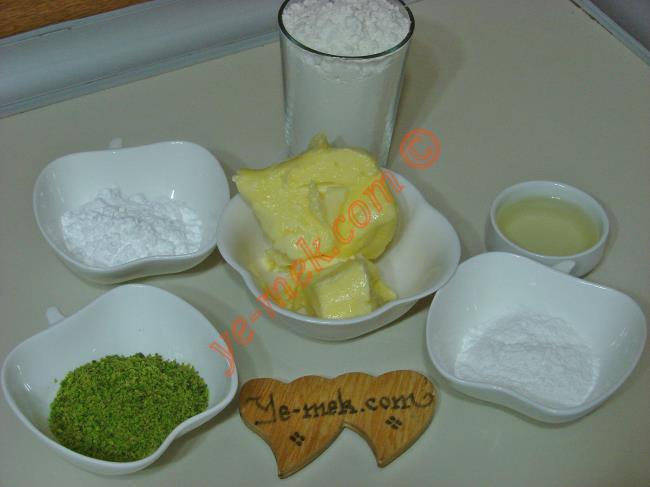 Fıstıklı Kurabiye İçin Gerekli Malzemeler :  <ul> <li>125 gr tereyağı</li> <li>5 yemek kaşığı sıvıyağ</li> <li>2 yemek kaşığı mısır nişastası</li> <li>2 yemek kaşığı pudra şekeri</li>         <li>2 yemek kaşığı yeşil toz fıstık</li>         <li>1,5 su bardağı kadar un</li> <li><strong>Üzeri İçin: </strong></li> <li>Yeşil toz fıstık</li>  </ul>
