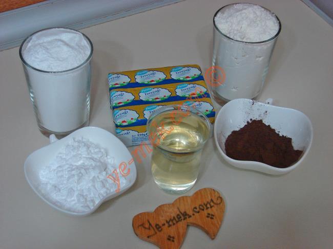 İki Renkli Spiral Kurabiye İçin Gerekli Malzemeler :  <ul> <li>250 gr tereyağı (oda sıcaklığında)</li>         <li>1 çay bardağı sıvıyağ</li> <li>1 su bardağı pudra şekeri</li> <li>4 yemek kaşığı buğday nişastası</li>         <li>2 yemek kaşığı dolusu kakao (Hamurun yarısı için)</li> <li>3,5-4 su bardağı arası un</li> </ul>