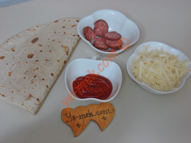 Lavaş Tostu İçin Gerekli Malzemeler :  <ul> <li>1 adet lavaş ekmeği</li> <li>5 adet küçük dilim sucuk</li> <li>Küçük bir kase rendelenmiş kaşar peynir</li>         <li>1 yemek kaşığı ketçap</li> </ul>
