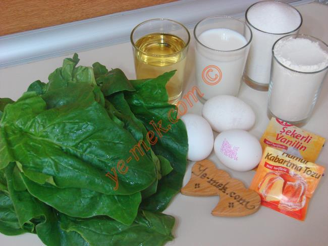 Ispanaklı Kek İçin Gerekli Malzemeler :  <ul> <li>3 adet yumurta (Oda ısısında) </li>         <li>1,5 su bardağı toz şeker</li>         <li>1 su bardağından 1 parmak az süt</li> <li>1 su bardağından 1 parmak az sıvı yağ</li>  <li>15 adet büyük boy ıspanak yaprağı</li> <li>1 paket kabartma tozu</li> <li>1 paket vanilya</li>         <li>2,5 su bardağı un + 4 yemek kaşığı un</li> </ul>