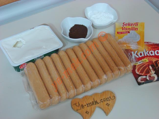 Tiramisu Topları İçin Gerekli Malzemeler :  <ul> <li>10 adet kedi dili bisküvi</li> <li>1/2 paket labne peyniri</li> <li>1 yemek kaşığı tepeleme pudra şekeri</li>         <li>1/2 paket vanilya</li> <li>1,5 tatlı kaşığı granül kahve (nescafe)</li>         <li>2,5 yemek kaşığı sıcak su</li> <li>Bulamak için 1,5 yemek kaşığı kakao</li> </ul>