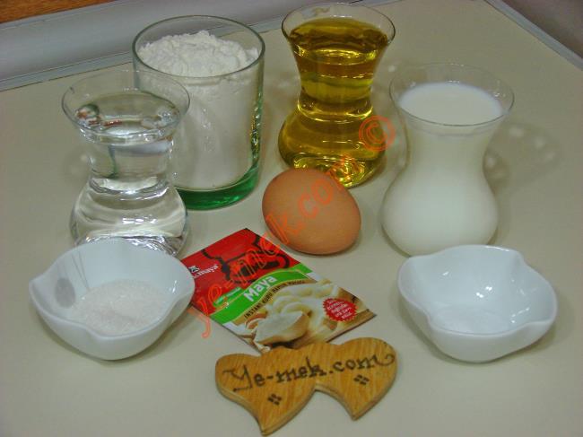 Kahvaltılık Mini Bazlama İçin Gerekli Malzemeler :  <ul> <li>1 çay bardağı ılık süt</li> <li>1 çay bardağı ılık su</li>  <li>1 çay bardağı zeytinyağı</li> <li>1 yemek kaşığı toz şeker</li>         <li>1 paket kuru maya</li> <li>1 tatlı kaşığı tuz</li> <li>4-4,5 su bardağı un</li> </ul>