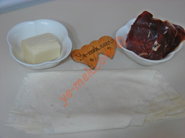 Fırında Paçanga Böreği İçin Gerekli Malzemeler :  <ul> <li>1 adet yufka</li>         <li>4 adet büyük dilim pastırma</li>         <li>5 yemek kaşığı rendelenmiş kaşar peynir</li>         <li><strong>Üzeri İçin:</strong></li>         <li>1 adet yumurta sarısı</li>         <li>Küçük bir çay bardağı süt</li> </ul>