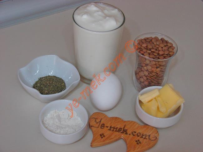 Yoğurtlu Mercimek Çorbası İçin Gerekli Malzemeler :  <ul> <li>1 çay bardağı yeşil mercimek</li>         <li>1 su bardağı dolusu yoğurt</li> <li>1 yemek kaşığı dolusu un</li>         <li>1 adet yumurta sarısı</li>         <li>5 su bardağı su</li>         <li>Tuz</li>         <li><strong>Üzeri İçin:</strong></li>         <li>1/2 yemek kaşığı tereyağı</li>         <li>1 çay kaşığı kuru nane</li>          </ul>