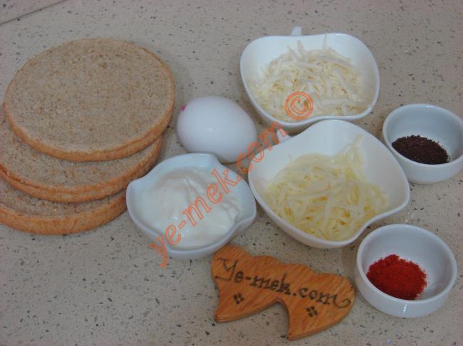 Acılı Ekmek Dilimleri İçin Gerekli Malzemeler :  <ul> <li>5 adet orta boy bayat ekmek dilimi</li>         <li>4 yemek kaşığı rendelenmiş kaşar peynir</li> <li>2 yemek kaşığı yoğurt</li> <li>1 adet yumurta</li>         <li>1 çay kaşığı sumak</li>         <li>1,5 tatlı kaşığı kırmızı pul biber</li>         <li>Az miktar tuz</li>          </ul>