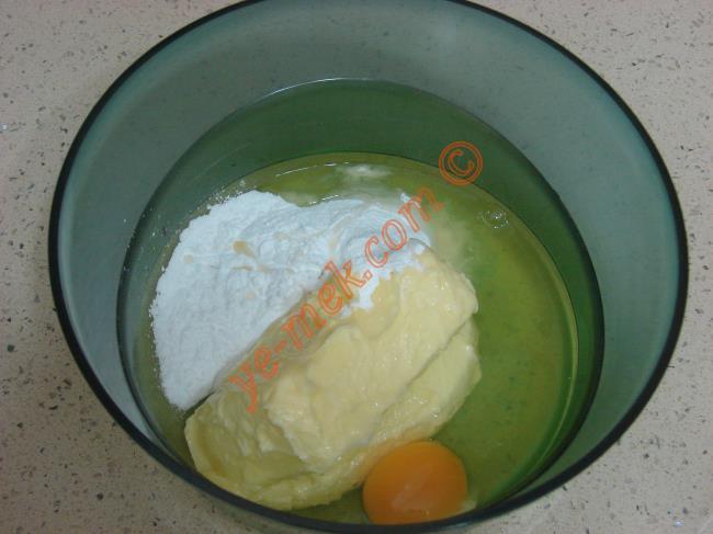 Kalburabastı tatlısının hamuru için; derin bir kap içine 250 gr oda sıcaklığındaki tereyağı koyun. Üzerine 2 adet yumurta kırın. Yarım su bardağı pudra şekeri ekleyin.