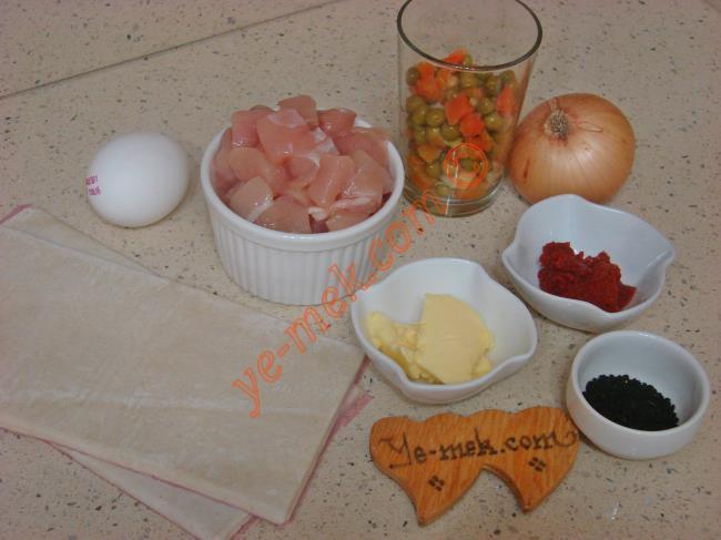 Tavuklu Talaş Kebabı İçin Gerekli Malzemeler :  <ul> <li>6 adet kare milföy</li> <li>500 gr kuşbaşı tavuk göğsü</li>         <li>1/2 su bardağı garnitür</li>         <li>1 adet orta boy soğan</li>         <li>1 çay kaşığı domates salçası</li>         <li>Tuz, karabiber</li> <li><strong>Üzeri İçin:</strong></li> <li>Yumurta sarısı</li>         <li>Çörek otu</li> </ul>