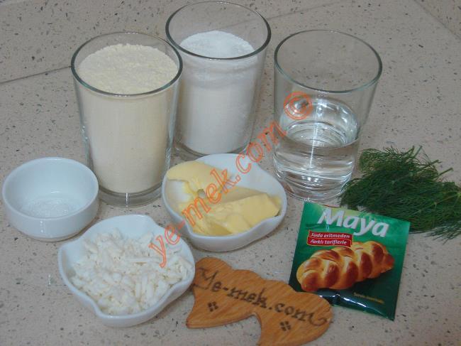 Peynirli Dereotlu Mısır Ekmeği İçin Gerekli Malzemeler :  <ul> <li>30 gr tereyağı (1 yemek kaşığı dolusu)</li> <li>1 çay kaşığı tuz</li>         <li>1/2 çay kaşığı toz şeker</li>         <li>1 su bardağı mısır unu</li>         <li>1/2 paket instant kuru maya</li> <li>1/2 su bardağı un</li>         <li>1/2 su bardağı ılık su</li> <li>1 tutam dereotu</li> <li>1,5 yemek kaşığı rendelenmiş beyaz peynir</li> </ul>