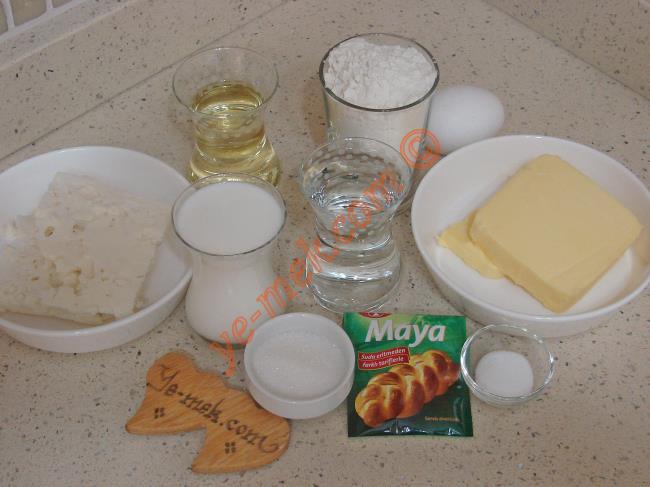 Peynirli Katmer Poğaça İçin Gerekli Malzemeler :  <ul> <li>1 çay bardağı ılık su</li>         <li>1 çay bardağı ılık süt</li>         <li>1 çay bardağından bir parmak az sıvıyağ</li> <li>1 tatlı kaşığı tuz</li>         <li>2 yemek kaşığı toz şeker</li> <li>1 paket instant kuru maya</li> <li>3,5 su bardağı un</li>         <li><strong>Ara Katlara Sürmek İçin:</strong></li>         <li>125 gr tereyağı (Oda Isısında)</li> <li><strong>İçi İçin:</strong></li> <li>Beyaz peynir</li>         <li><strong>Üzeri İçin:</strong></li>         <li>2 adet yumurta sarısı</li> </ul>