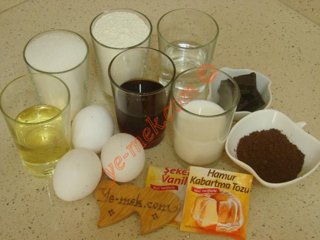 Çaylı Islak Kek İçin Gerekli Malzemeler :  <ul> <li>3 adet yumurta</li> <li>1 su bardağı toz şeker</li> <li>1/2 su bardağı demli çay (Oda ısısında soğumuş)</li> <li>1/2 su bardağı süt</li> <li>1/2 su bardağı sıvıyağ</li> <li>3 yemek kaşığı kakao</li>         <li>1 paket kabartma tozu</li> <li>1 paket vanilya</li> <li>1,5 su bardağı + 1 yemek kaşığı tepeleme un</li> <li><strong>Sosu İçin:</strong></li> <li>1,5 su bardağı süt</li>         <li>1/2 su bardağı sıvıyağ</li>         <li>1/2 su bardağı su</li>         <li>3,5 yemek kaşığı toz şeker</li>         <li>2 yemek kaşığı kakao</li>         <li>5 parça bitter çikolata (isteğe bağlı)</li> </ul>