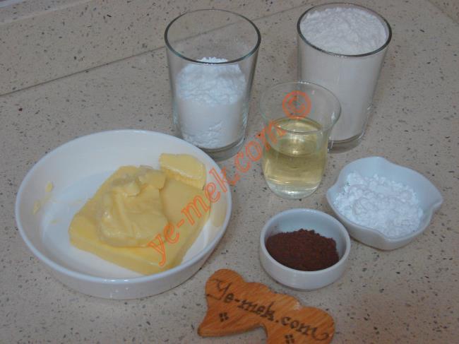 Papatya Kurabiye İçin Gerekli Malzemeler :  <ul> <li>125 gr tereyağı (oda sıcaklığında)</li>         <li>1/2 çay bardağı sıvıyağ</li> <li>1/2 su bardağı pudra şekeri</li> <li>2 yemek kaşığı buğday nişastası</li>         <li>1 yemek kaşığı dolusu kakao (Hamurun yarısı için)</li> <li>2 su bardağı un</li> </ul>
