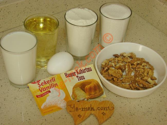 Yalancı Baklava Tatlısı İçin Gerekli Malzemeler :  <ul> <li>1 adet yumurta</li> <li>1 su bardağı süt</li> <li>1 su bardağı sıvıyağ</li> <li>1 paket vanilya</li>  <li>1 paket kabartma tozu</li> <li>4 su bardağı un</li>         <li>5 yemek kaşığı elle parçalanmış ceviz içi</li>  <li><strong>Şerbeti İçin:</strong></li> <li>2,5 su bardağı toz şeker</li> <li>3 su bardağı su</li>         <li>4 damla limon suyu</li> </ul>