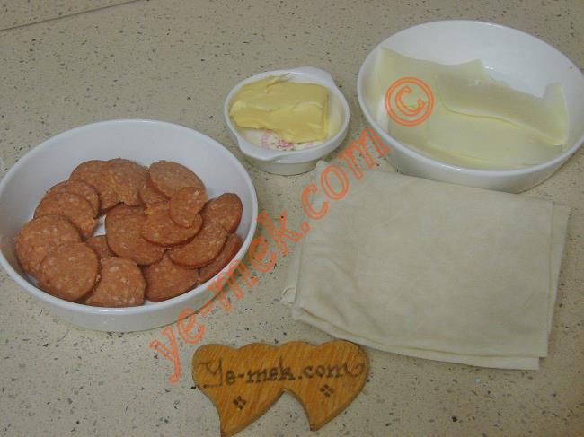 Tavada Çıtır Börek İçin Gerekli Malzemeler :  <ul> <li>2 adet yufka</li> <li>Tereyağı</li>         <li>Sucuk dilimleri</li> <li>Kaşar peynir dilimleri</li> </ul>