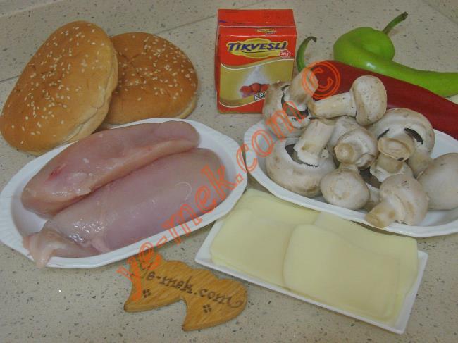 Tavuklu Ekmek Kebabı İçin Gerekli Malzemeler :  <ul> <li>500 gr tavuk göğüsü</li>         <li>1/2 paket mantar</li>         <li>2 adet yuvarlak sandviç ekmeği</li>         <li>1 adet kırmızı kapya biber</li>         <li>1 adet çerliston biber</li>         <li>1/2 paket süt kreması</li>         <li>3 yemek kaşığı zeytinyağı</li>         <li>Tuz, karabiber</li>         <li><strong>Üzeri İçin:</strong></li>         <li>Kaşar peynir dilimleri</li> </ul>