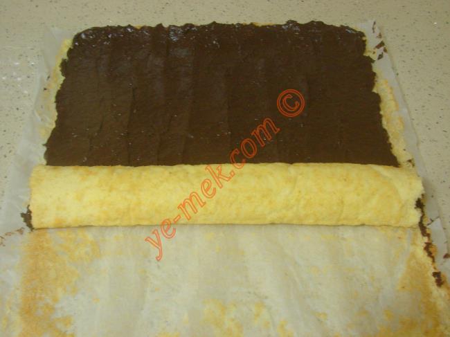 İsteğe göre keki yağlı kağıttan tamamen çıkartıp, kremayı bu şekilde sürüp, rulo yapabilirsiniz.