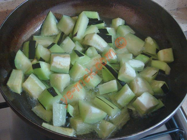 Diğer yandan 3 adet kemer patlıcanı alacalı olarak soyun. Büyük küpler halinde kesin. Kızgın yağ içinde kızartın.
