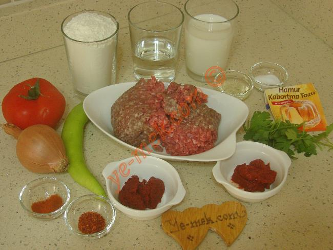 Tavada Lahmacun İçin Gerekli Malzemeler :  <ul>         <li><strong>Hamuru İçin:</strong></li> <li>1 su bardağından 2 parmak eksik ılık süt</li> <li>Yarım su bardağı ılık su</li> <li>1 yemek kaşığı sıvı yağ</li> <li>1 tatlı kaşığı tuz</li> <li>1/2 paket kabartma tozu</li> <li>3 su bardağı un</li>         <li><strong>İç Harcı İçin:</strong></li> <li>250 gr kıyma</li>         <li>1 adet soğan</li>         <li>1 adet büyük boy yeşil biber</li>         <li>1 adet orta boy domates</li>         <li>1/2 yemek kaşığı domates salçası</li>         <li>1/2 yemek kaşığı biber salçası</li>         <li>2 yemek kaşığı sıvı yağ</li>         <li>1 tutam maydanoz</li>         <li>Tuz, pulbiber, kırmızı toz biber</li>  </ul>