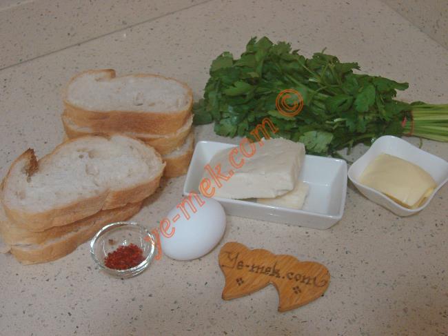 Fırında Maydanozlu Ekmek Dilimleri İçin Gerekli Malzemeler :  <ul> <li>6 dilim ekmek</li> <li>1 yemek kaşığı tereyağı (Oda sıcaklığında)</li> <li>100 gr beyaz peynir</li> <li>2 tutam maydanoz</li> <li>1 adet yumurta</li> <li>Kırmızı pulbiber</li> </ul>