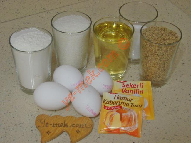 Hindistan Cevizli Şerbetli Tatlı İçin Gerekli Malzemeler :  <ul> <li>4 adet yumurta</li> <li>1/2 su bardağı toz şeker</li> <li>1 su bardağı sıvı yağ</li>         <li>1 su bardağı hindistan cevizi</li> <li>1 su bardağı çekilmiş ceviz</li> <li>1 paket vanilya</li> <li>1 paket kabartma tozu</li>         <li>1 su bardağı elenmiş un</li> <li><strong>Şerbeti İçin:</strong></li> <li>2 su bardağı toz şeker</li> <li>2,5 su bardağı su</li>         <li><strong>Üzeri İçin:</strong></li> <li>2 paket krem şanti tozu</li> <li>1 su bardağı soğuk süt</li>         <li>Bolca hindistan cevizi</li> </ul>