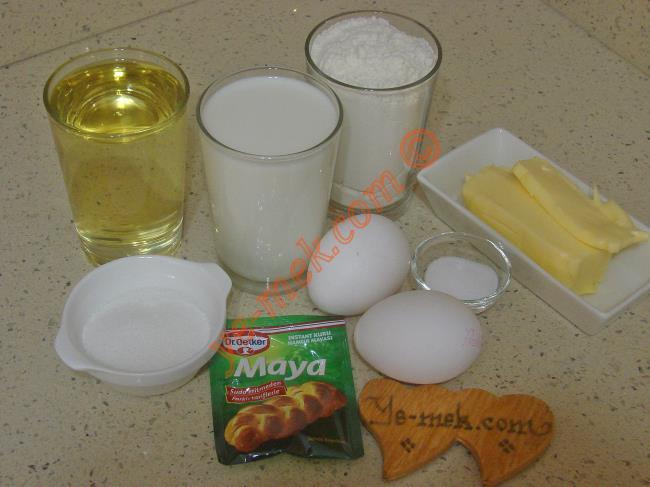 Katmerli Çörek İçin Gerekli Malzemeler :  <ul> <li>1 su bardağı ılık süt</li>         <li>2 yemek kaşığı toz şeker</li>         <li>1 su bardağı sıvıyağ</li> <li>1 paket instant kuru maya</li>         <li>2 yumurta akı (sarıları üzerine)</li> <li>1 tatlı kaşığı tuz</li> <li>4,5 su bardağı un</li>         <li><strong>Ara Katlara Sürmek İçin:</strong></li>         <li>100 gr yumuşak tereyağı</li>         <li><strong>Üzeri İçin:</strong></li>         <li>2 adet yumurta sarısı</li> </ul>