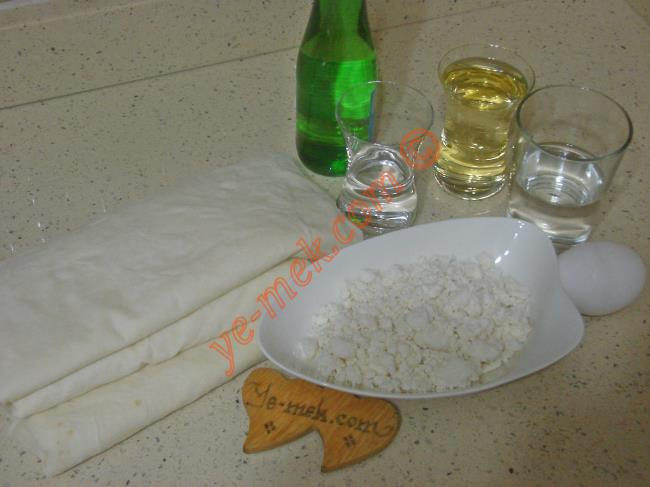 Sodalı Peynirli Börek İçin Gerekli Malzemeler :  <ul> <li>3 adet yufka</li>         <li><strong>Sosu İçin:</strong>         <li>1 çay bardağı sıvı yağ</li>         <li>1/2 çay bardağı su</li> <li><strong>İç Harcı İçin:</strong> <li>Beyaz peynir ya da lor peynir</li>         <li><strong>Üzeri İçin:</strong>         <li>1 şişe soda</li>         <li>1/2 su bardağı su</li>         <li>1 adet yumurta sarısı</li>   </ul>Sodalı peynirli börek yapımında; ilk olarak böreğin sosunu hazırlayın. Bir kap içine 1 çay bardağı sıvı yağ ve yarım çay bardağı su ekleyip, karıştırın.