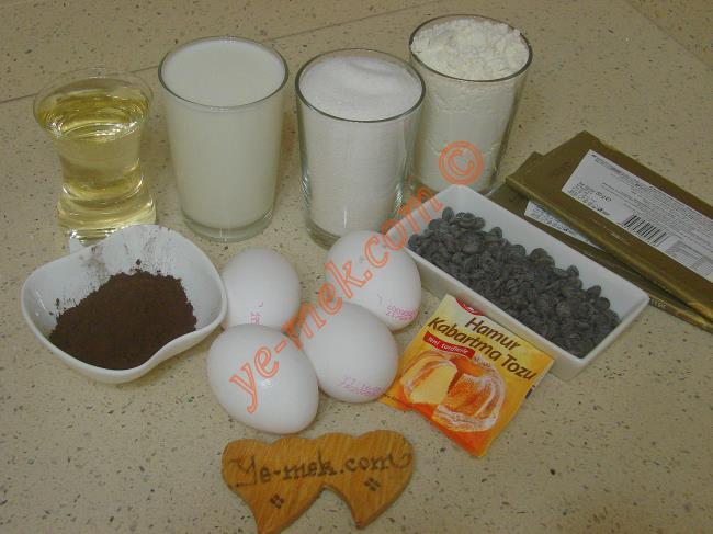 Çikolatalı Islak Kek İçin Gerekli Malzemeler :  <ul> <li>4 adet yumurta</li> <li>1 su bardağı toz şeker</li> <li>1 su bardağı süt</li> <li>1 çay bardağı sıvı yağ</li> <li>3 yemek kaşığı kakao</li>         <li>1 paket kabartma tozu</li>         <li>2 su bardağı un</li> <li>1 çimdik tuz</li>         <li><strong>Üzeri İçin:</strong></li>         <li>Damla çikolata</li> <li><strong>Sosu İçin:</strong></li> <li>1 paket bitter çikolata (80 gr)</li>         <li>1 paket sütlü çikolata (80 gr)</li>         <li>1 çay bardağı süt</li> </ul>