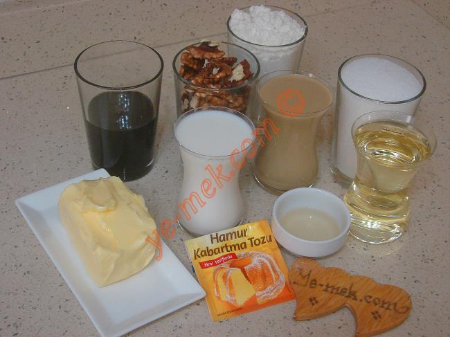 Nevzine Tatlısı İçin Gerekli Malzemeler :  <ul>         <li>125 gr tereyağı (Oda sıcaklığında)</li> <li>1 çay bardağı sıvı yağ</li>         <li>1 çay bardağı süt</li>         <li>1 çay bardağı tahin</li> <li>2 yemek kaşığı sirke</li>         <li>1 paket kabartma tozu</li>         <li>4 su bardağı un</li>         <li>1 su bardağı orta dövülmüş ceviz</li>         <li><strong>Şerbeti İçin:</strong>         <li>2,5 su bardağı su</li>         <li>2 su bardağı toz şeker</li>         <li>3 damla limon suyu</li>         <li>1/2 su bardağı dut ya da üzüm pekmezi</li>         <li><strong>Üzeri İçin:</strong>         <li>Tahin</li>         <li>Yeşil toz fıstık</li>  </ul>İlk olarak nevzine tatlısının şerbetini hazırlayın. Orta boy bir tencere içine 2 buçuk su bardağı su ve 2 su bardağı toz şeker koyun. Tencereyi ocak üzerine alıp, şeker eriyene kadar sürekli karıştırın. Ardından şerbeti kaynamaya bırakın. Kaynayan şerbetin içine 3 damla limon suyu ekleyip, 10-15 dakika kadar daha kaynamaya bırakın.