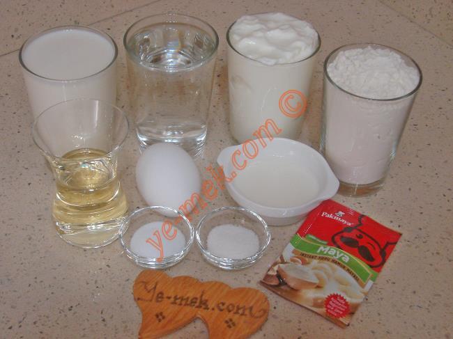 Göçmen Böreği İçin Gerekli Malzemeler :  <ul> <li>1 su bardağı ılık süt</li>         <li>1 su bardağı ılık su</li> <li>1 paket instant kuru maya</li> <li>1 tatlı kaşığı toz şeker</li> <li>1,5 tatlı kaşığı tuz</li>         <li>1 adet yumurta akı (sarısı üzerine)</li>         <li>5,5 su bardağı un</li> <li><strong>Sosu İçin:</strong></li> <li>1 su bardağı yoğurt</li>         <li>Yarım çay bardağı sıvı yağ</li>         <li>1 adet yumurta sarısı</li>         <li>4 yemek kaşığı süt</li> </ul>