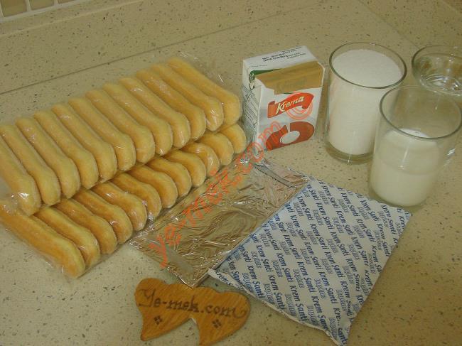 Şerbetli Kedi Dili Tatlısı İçin Gerekli Malzemeler :  <ul> <li>1 paket kedi dili bisküvi (24 adet)</li>         <li><strong>Kreması İçin:</strong></li>         <li>1 paket krem şanti tozu</li>         <li>1/2 su bardağı soğuk süt</li> <li><strong>Şerbeti İçin:</strong></li> <li>1,5 su bardağı toz şeker</li>         <li>1,5 su bardağı su</li>         <li>1 tatlı kaşığı limon suyu</li>         <li><strong>Çikolata Sosu İçin:</strong></li>         <li>1 paket süt kreması (200 ml)</li>         <li>1 paket bitter çikolata (80 gr)</li> </ul>