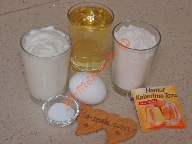 Sıvı Yağlı Poğaça İçin Gerekli Malzemeler :  <ul> <li>1 su bardağı sıvı yağ</li> <li>1 su bardağı yoğurt</li> <li>1 adet yumurta akı (Sarısı üzerine)</li>         <li>1 tatlı kaşığı tuz</li> <li>1 paket kabartma tozu</li>         <li>3,5 su bardağı un</li>         <li><strong>İç Malzemesi İçin:</strong></li>         <li>150 gr lor peynir</li>         <li>1 tutam maydanoz</li> <li><strong>Üzeri İçin:</strong></li> <li>Yumurta sarısı</li> </ul>
