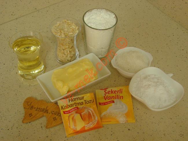 Hindistan Cevizli Fındıklı Kurabiye İçin Gerekli Malzemeler :  <ul> <li>125 gr tereyağı (oda sıcaklığında)</li>         <li>1 küçük çay bardağı sıvıyağ</li> <li>1/2 çay bardağından 1 parmak fazla fındık kırığı</li> <li>2 yemek kaşığı hindistan cevizi</li> <li>4 yemek kaşığı dolusu pudra şekeri</li> <li>1 paket kabartma tozu</li> <li>2,5 su bardağı un</li>         <li><strong>Üzeri İçin:</strong></li>         <li>2 yemek kaşığı hindistan cevizi</li>         <li>2 yemek kaşığı fındık kırığı</li>  </ul>