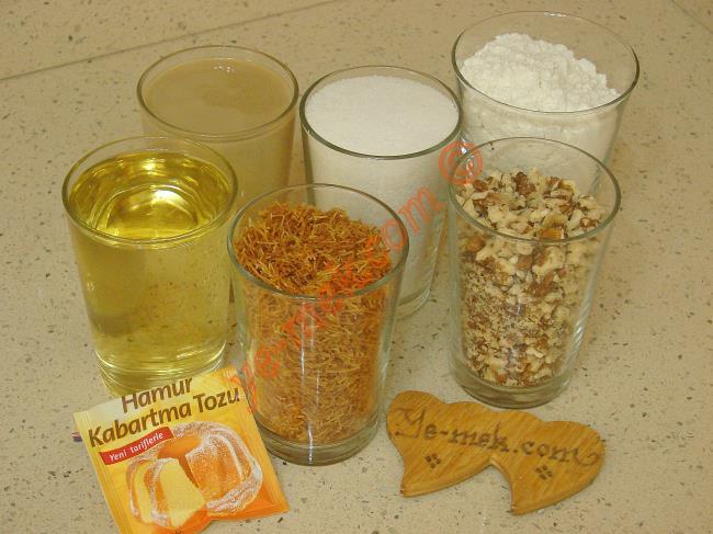 Kadayıflı Tahinli Kurabiye İçin Gerekli Malzemeler :  <ul> <li>1 su bardağı hazır kavrulmuş kadayıf</li> <li>1 su bardağı sıvı yağ</li> <li>1 su bardağı tahin</li>         <li>1 su bardağı toz şeker</li>         <li>1 su bardağı orta dövülmüş ceviz</li>         <li>1 paket kabartma tozu</li>         <li>4,5 su bardağı un</li> <li><strong>Üzeri İçin:</strong> <li>Pudra şekeri</li> </ul>