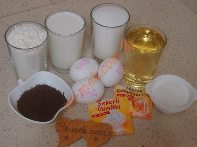 Karakız Tatlısı İçin Gerekli Malzemeler :  <ul> <li>3 adet yumurta</li> <li>1 su bardağı toz şeker</li> <li>1 su bardağı süt</li> <li>1 su bardağı sıvı yağ</li> <li>3 yemek kaşığı kakao</li>         <li>1 paket kabartma tozu</li> <li>1 paket vanilya</li> <li>2 su bardağı un</li> <li><strong>Şerbeti İçin:</strong></li> <li>2 su bardağı su</li>         <li>1 su bardağı toz şeker</li>         <li><strong>Kreması İçin:</strong></li>         <li>4 su bardağı süt</li>         <li>2 yemek kaşığı un</li>         <li>2 yemek kaşığı pirinç unu</li>         <li>1 çay bardağı toz şeker</li>         <li><strong>Üzeri İçin:</strong></li>         <li>Rendelenmiş çikolata, hindistan cevizi</li> </ul>İlk olarak tatlının şerbetini hazırlayın. Küçük bir tencere içine 2 su bardağı su ve 1 su bardağı toz şeker koyun. Ocak üzerine alıp, şeker eriyene kadar sürekli karıştırın. Ardından şerbeti kaynamaya bırakın. Şerbet kaynamaya başlayınca, kısık ateşte 5 dakika daha kaynatıp, ocaktan alın. Soğumaya bırakın.
