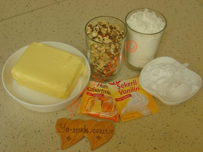 Cevizli Un Kurabiyesi İçin Gerekli Malzemeler :  <ul> <li>250 gr tereyağı ya da margarin (Oda sıcaklığında)</li> <li>3,5 yemek kaşığı tepeleme pudra şekeri</li> <li>1 su bardağı ceviz kırığı</li>         <li>1 paket kabartma tozu</li>         <li>1 paket vanilya</li>         <li>3 su bardağı un</li> <li><strong>Üzeri İçin:</strong> <li>Pudra şekeri</li> </ul>