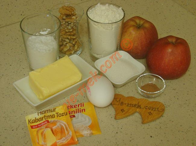Elmalı Kurabiye İçin Gerekli Malzemeler :  <ul> <li>125 gr tereyağı (Oda sıcaklığında)</li>         <li>2,5 yemek kaşığı toz şeker</li>         <li>Yarım su bardağı nişasta</li>         <li>1 adet yumurta</li>         <li>Yarım paket kabartma tozu</li>         <li>1 paket vanilya</li>         <li>2 su bardağı un</li> <li><strong>İç Harcı İçin:</strong> <li>2 adet büyük boy elma</li>         <li>2 yemek kaşığı toz şeker</li>          <li>1 çay kaşığı tarçın</li>          <li>1 çay bardağı az dövülmüş ceviz</li>          <li><strong>Üzeri İçin:</strong>          <li>Pudra şekeri</li>  </ul>