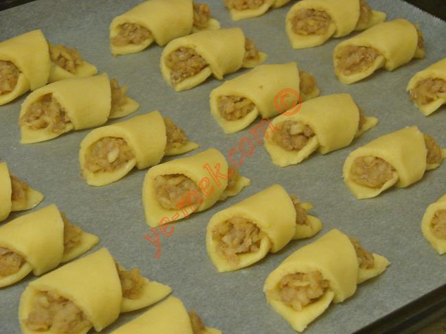 Hazırladığınız elmalı kurabiyeleri yağlı kağıt serili fırın tepsisi içine dizin.
