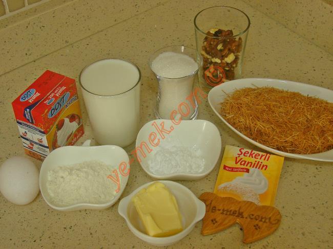 Kadayıflı Muhallebi Tatlısı İçin Gerekli Malzemeler :  <ul> <li>150 gr hazır fırınlanmış kadayıf</li> <li>1 yemek kaşığı toz şeker</li> <li>1 yemek kaşığı tereyağı</li>         <li>4 yemek kaşığı kırık ceviz</li> <li><strong>Muhallebisi İçin:</strong></li>         <li>3 su bardağı süt</li>         <li>3 yemek kaşığı un</li>         <li>3 tatlı kaşığı buğday nişastası</li>         <li>1 küçük çay bardağı toz şeker</li>         <li>1 adet yumurta sarısı</li>         <li>1 paket vanilya</li>         <li>1/2 paket süt kreması</li> </ul>