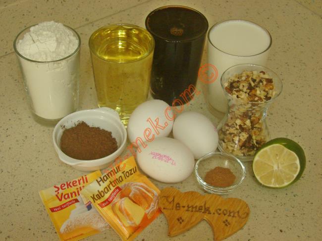 Pekmezli Kek İçin Gerekli Malzemeler :  <ul> <li>3 adet yumurta</li>         <li>1 su bardağından biraz fazla pekmez</li>         <li>1 su bardağı sıvı yağ</li> <li>1 su bardağı süt</li>         <li>1 çay bardağı iri dövülmüş ceviz</li>         <li>1 yemek kaşığı kakao</li>         <li>1 çay kaşığı tarçın</li>         <li>4 damla limon suyu</li> <li>1 paket kabartma tozu</li> <li>1 paket vanilya</li>         <li>3 su bardağı un</li> </ul>