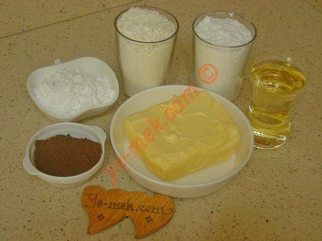 Şekilli Kurabiye İçin Gerekli Malzemeler :  <ul> <li>250 gr tereyağı (oda sıcaklığında)</li>         <li>1 çay bardağı sıvıyağ</li> <li>1 su bardağı pudra şekeri</li> <li>4 yemek kaşığı buğday nişastası</li>         <li>2 yemek kaşığı dolusu kakao (Hamurun yarısı için)</li> <li>4 su bardağı un</li> </ul>