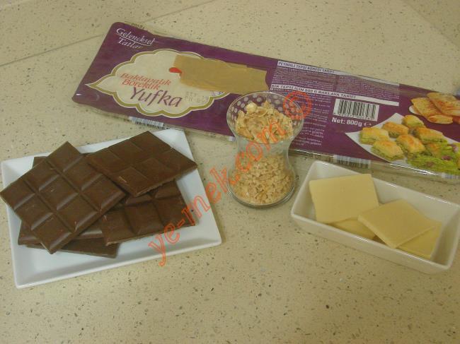 Çikolatalı Pratik Tatlı İçin Gerekli Malzemeler :  <ul> <li>5 yaprak hazır baklavalık yufka</li> <li>3 paket sütlü çikolata (240 gr)</li> <li>1 çay bardağı iri dövülmüş fındık</li>         <li><strong>Üzeri İçin:</strong></li>         <li>1 paket beyaz çikolata</li>         <li>Yeşil toz fıstık ya da dövülmüş fındık</li> </ul>