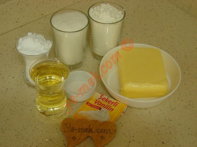 Pişmaniye Kurabiye İçin Gerekli Malzemeler :  <ul> <li>250 gr tereyağı (Oda sıcaklığında)</li> <li>1 çay bardağı pudra şekeri</li> <li>1 çay bardağı sıvı yağ</li>         <li>1 su bardağı hindistan cevizi</li>         <li>1 paket vanilya</li>         <li>3 su bardağı un</li> <li><strong>Bulamak İçin:</strong> <li>1 çay bardağı hindistan cevizi</li>         <li>1/2 çay bardağı pudra şekeri</li>         <li>1 yemek kaşığı toz şeker</li> </ul>