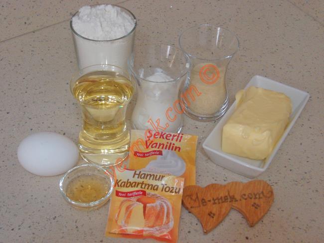 Gül Tatlısı İçin Gerekli Malzemeler :  <ul> <li>125 gr tereyağı (Oda sıcaklığında)</li> <li>1 çay bardağı sıvıyağ</li> <li>1/2 çay bardağı yoğurt</li> <li>1 adet yumurta</li> <li>1/2 çay bardağı irmik</li> <li>1 tatlı kaşığı sirke</li> <li>1 paket vanilya</li> <li>1 paket kabartma tozu</li> <li>3 su bardağı un</li> <li><strong>Şerbeti İçin:</strong></li> <li>3,5 su bardağı su</li> <li>3,5 su bardağı toz şeker</li> <li>Çeyrek limon suyu</li>         <li><strong>Üzeri İçin:</strong></li>         <li>Fındık</li> </ul>Gül tatlısı için; ilk olarak şerbeti hazırlayın. Orta boy derin bir tencere içine 3 buçuk su bardağı su ve 3 buçuk su bardağı toz şeker koyun. Tencereyi ocak üzerine alın. Şeker eriyene kadar karıştırıp, kaynamaya bırakın. Şerbet kaynamaya başladıktan sonra çeyrek limon suyu ekleyip, karıştırın. Ocağın altını biraz kısıp, 15 dakika kadar daha kaynatın. Ardından ocaktan alıp, soğumaya bırakın.