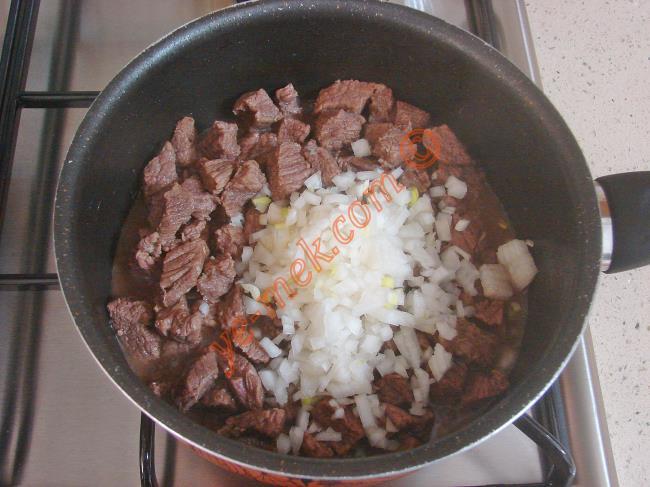 Ardından etlerin üzerini hafifçe geçecek kadar sıcak su dökün. Etler suyunu çekip, yumuşayana kadar pişirin.   Daha sonra yumuşayan etlerin üzerine 2-3 yemek kaşığı sıvı yağ, 1 adet orta boy ince ince doğranmış soğan ve 1 diş ince ince kıyılmış sarımsak ekleyin.