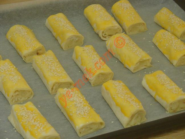 Kestiğiniz börekleri yağlı kağıt serili fırın tepsisi içine dizin. Üzerlerine yumurta sarısı sürüp, susam serpiştirin.