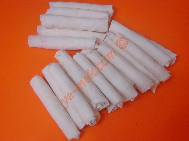 Sardığınız sigara böreklerin uç kısımlarını suya batırın. Ardından yufkaya yapışmasını sağlayın.