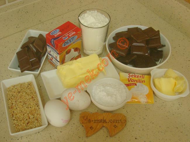 Çikolatalı Mini Tart İçin Gerekli Malzemeler :  <ul> <li>150 gr tereyağı (Oda sıcaklığında)</li>         <li>3 yemek kaşığı pudra şekeri</li>         <li>2 adet yumurta sarısı</li>         <li>2 yemek kaşığı soğuk su</li>         <li>1 paket vanilya</li>         <li>2,5 su bardağı un</li> <li><strong>Çikolatalı Krema İçin:</strong> <li>1 kutu sıvı krema (200 ml)</li>         <li>100 gr sütlü çikolata</li>         <li>100 gr bitter çikolata</li>         <li>50 gr tereyağı</li>         <li><strong>Tartın Kenarları İçin:</strong>         <li>100 gr sütlü çikolata</li>         <li>Kavrulmuş fındık kırığı</li>  </ul>